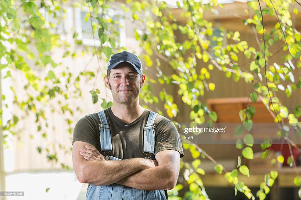 Portrait of farmer with arms folded, smiling : Stock Photo