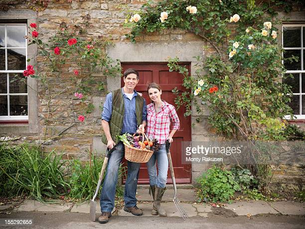 Portrait of farming couple with basket of organic vegetables and gardening tools standing in front of farmhouse doorway