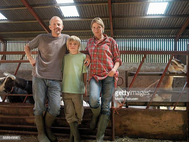 Portrait of farming family in barn with goats