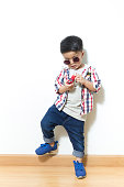 portrait of fashion boy with toy. .Asian cute boy on white wall.