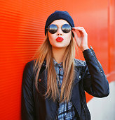 Portrait of fashionable blonde girl with red lipstick wearing a rock black style having fun outdoors in the city