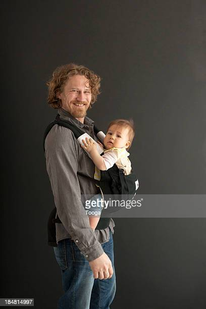 Portrait of father and daughter in baby sling