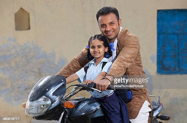 Portrait of father and daughter on motorbike