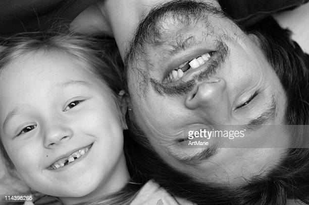 Portrait of father and daughter without a tooth