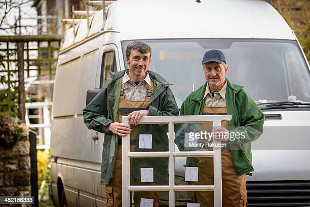 Portrait of father and son builders holding new window for installation
