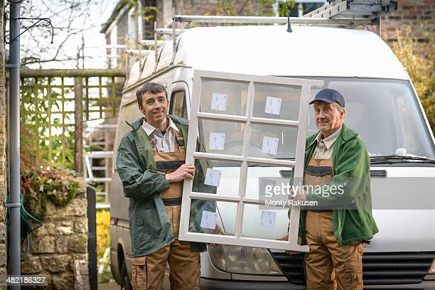 Portrait of father and son builders holding new window