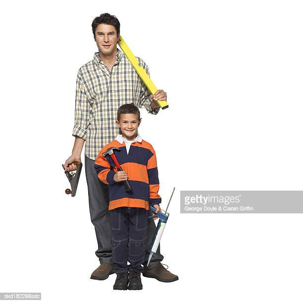 Portrait of father and son (8-9) holding work tools