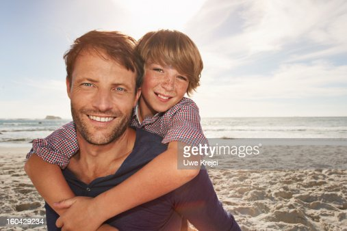 Portrait of father and son hugging, outdoors : Stock Photo