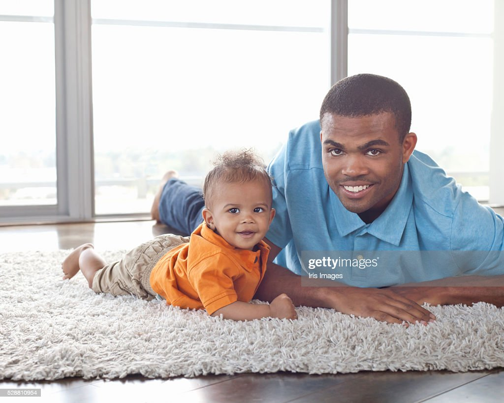 Portrait of father and son (6-12 months) lying on floor