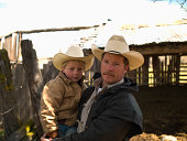 Young cowboy and father in corral of family ranch in Big Timber, Montana