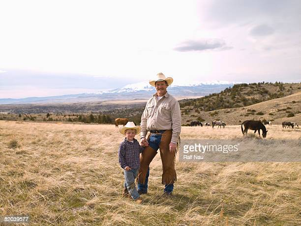 Portrait of father and son on range with wild horses