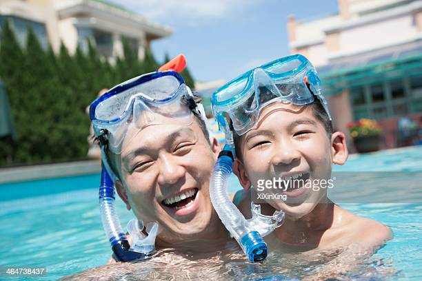Portrait of father and son with snorkeling equipment in the pool