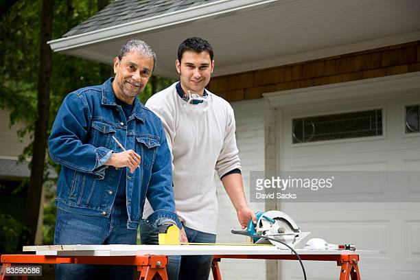 Portrait of father and son working driveway