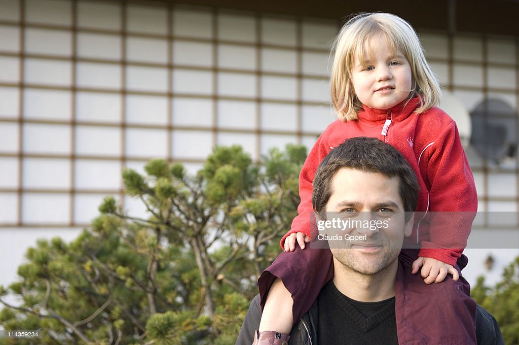 portrait of father carrying young daughter on his shoulders : Stock Photo