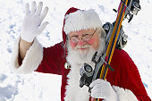 Portrait of Father Christmas Holding Skis and Waving