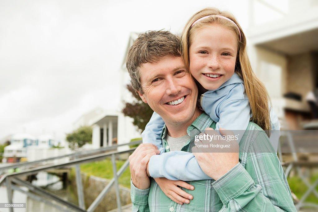 Portrait of father giving daughter (8-9) piggyback ride : Foto de stock