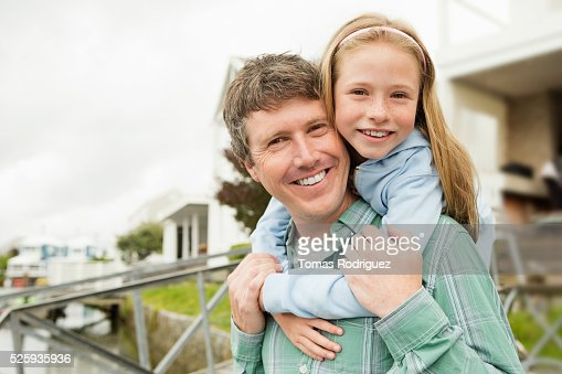 Portrait of father giving daughter (8-9) piggyback ride : Foto de stock