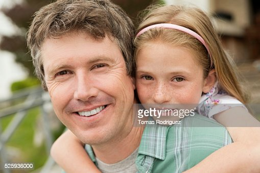 Portrait of father giving daughter (8-9) piggyback ride : Foto stock