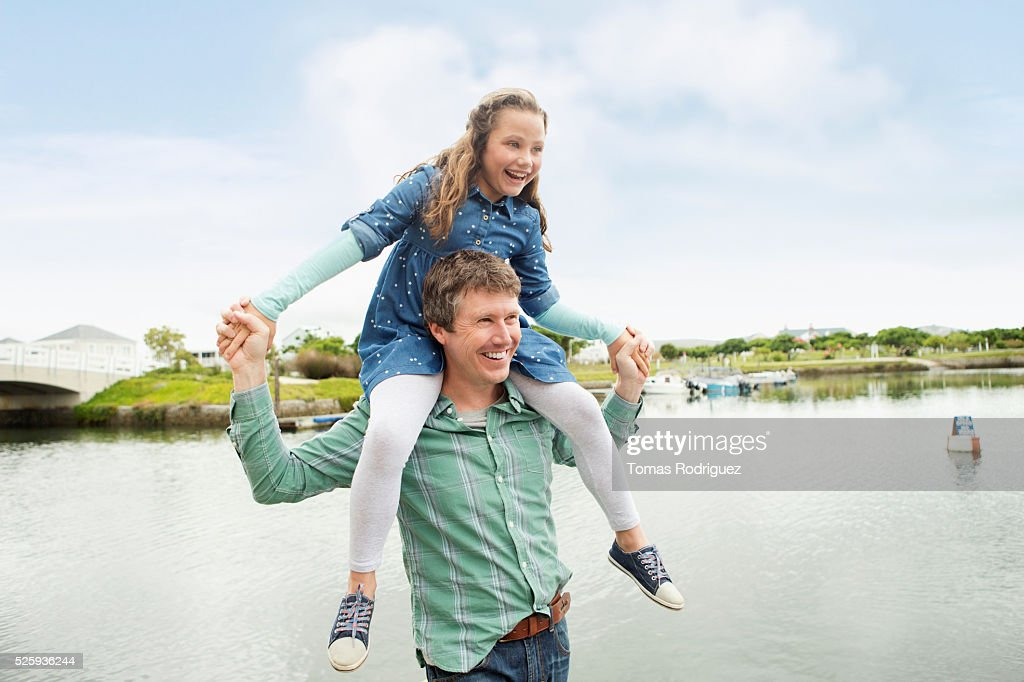 Portrait of father giving daughter (6-7) piggyback ride : Stock Photo