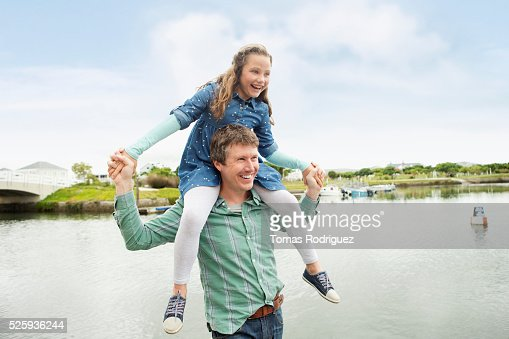 Portrait of father giving daughter (6-7) piggyback ride : Stockfoto