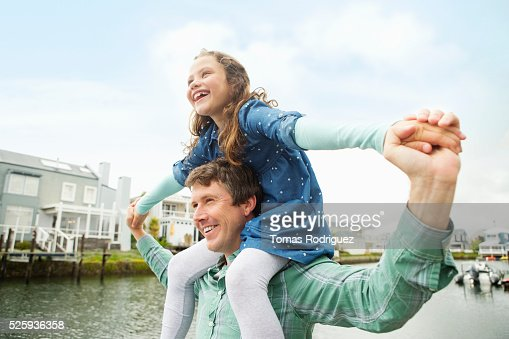 Portrait of father giving daughter (6-7) piggyback ride : Photo