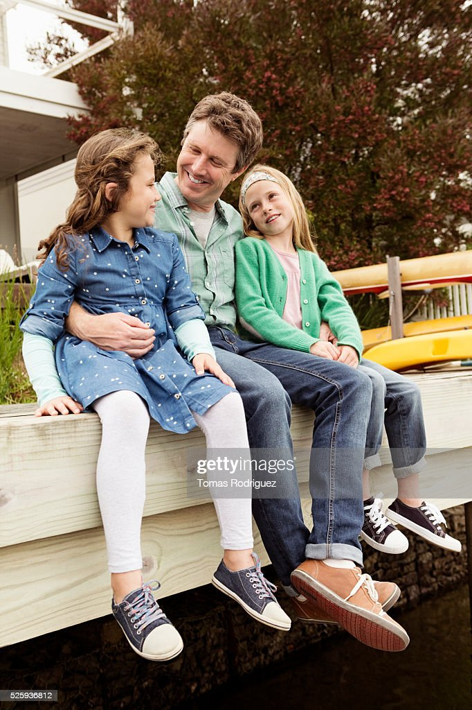 Portrait of father relaxing with daughters (6-7), (8-9) : Stock-Foto