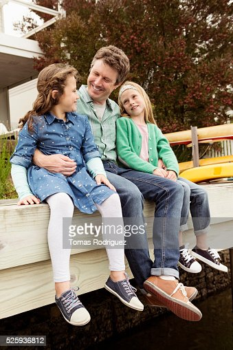 Portrait of father relaxing with daughters (6-7), (8-9) : Stockfoto
