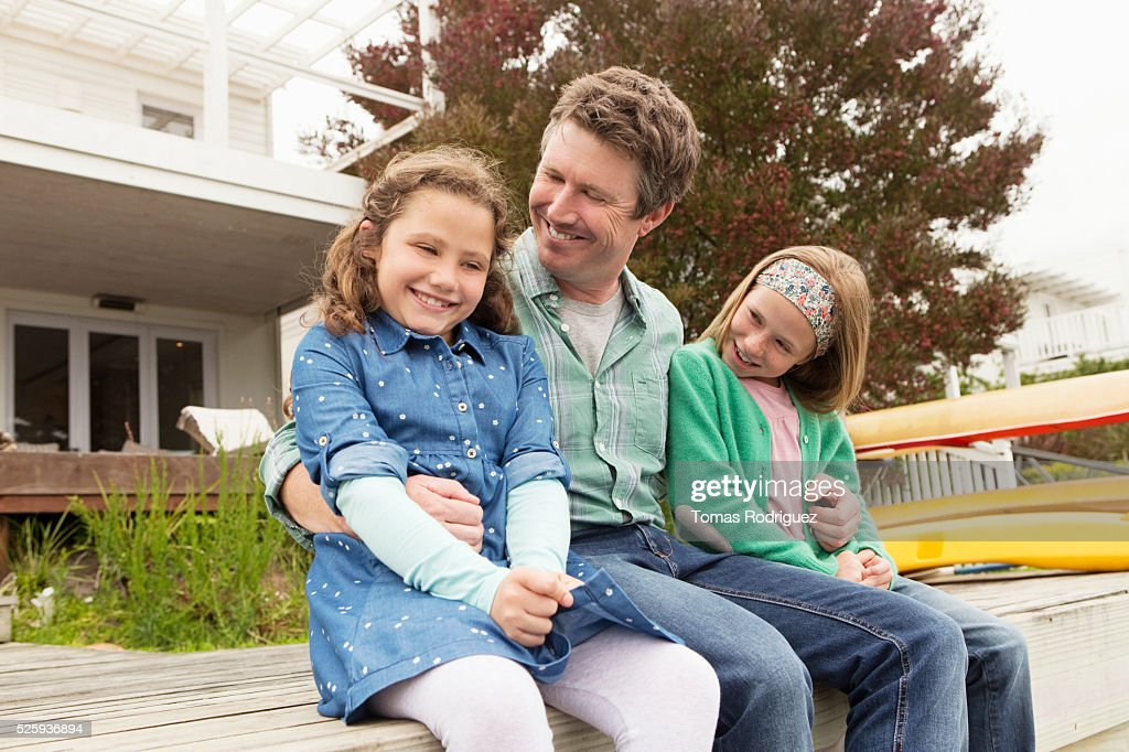 Portrait of father relaxing with daughters (6-7), (8-9) : Foto stock