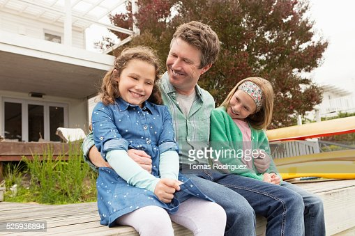 Portrait of father relaxing with daughters (6-7), (8-9) : Stock Photo