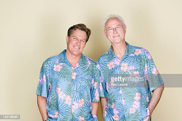 Portrait of father with adult son wearing Hawaiian shirts