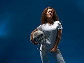 Portrait of female american footballer holding helmet