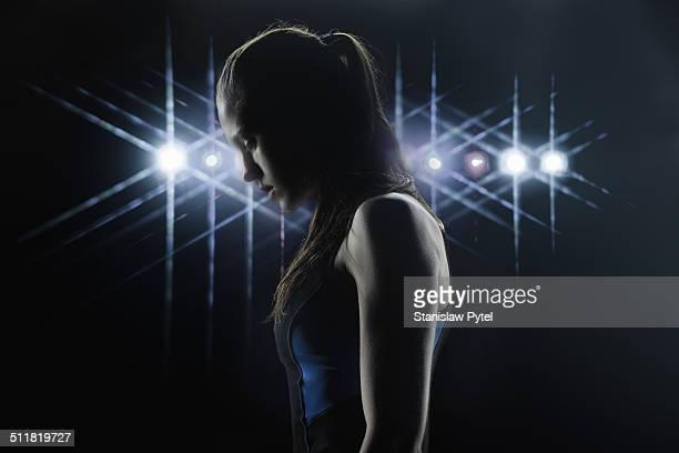 Portrait of female athlete, stadium lights behind