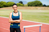 Portrait of female athlete standing beside hurdle with arms crossed