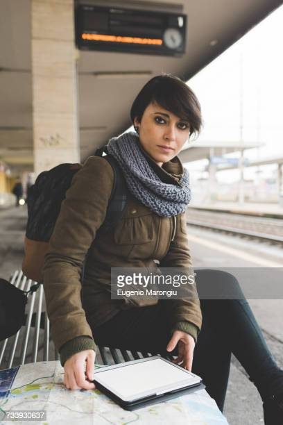 Portrait of female backpacker with map and digital tablet on railway platform