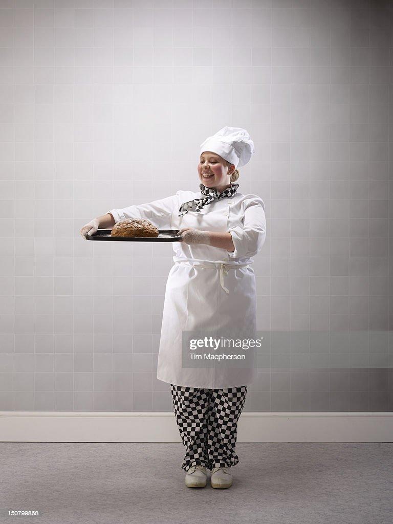 Portrait of Female baker holding bread