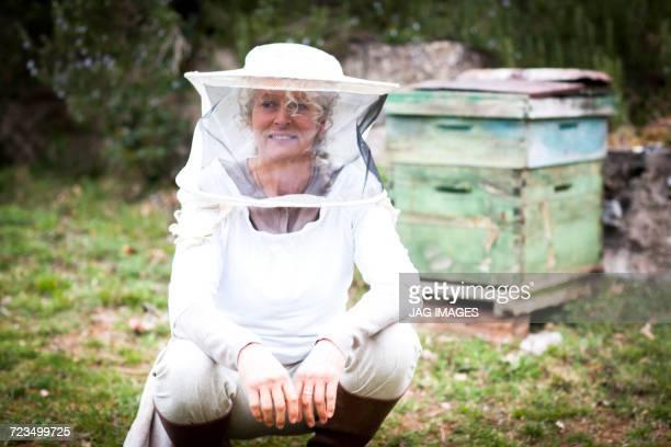 Portrait of female beekeeper crouching in garden