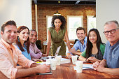 Portrait Of Female Boss With Team In Meeting Smiling At Camera