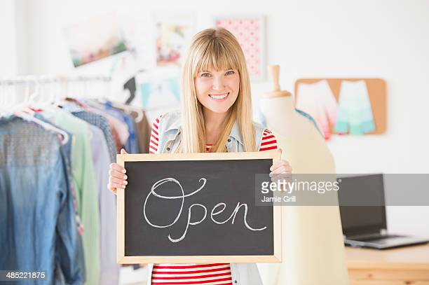 Portrait of female business owner holding open sign