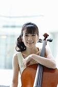 Portrait of female cellist,smiling,close up.
