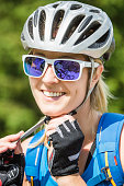 Portrait of female cyclist wearing helmet and sunglasses
