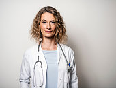 Portrait of confident smiling female doctor. Mid adult medical professional is wearing lab coat and stethoscope. She is standing against gray wall in hospital.
