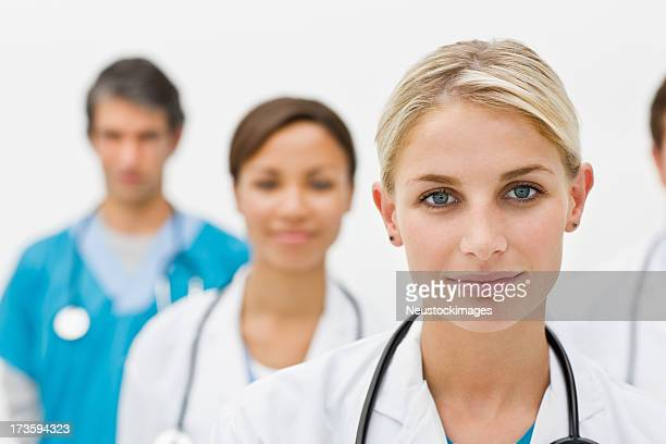 Portrait of female doctor with colleagues in the background
