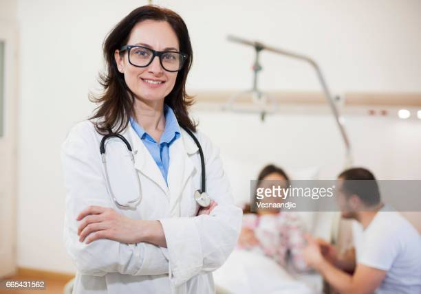Portrait Of Female Doctor With Patient In Background