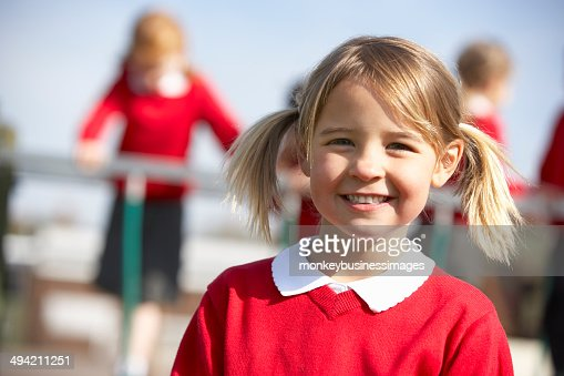 Portrait Of Female Elementary School Pupil In Playground : Stock Photo