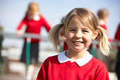 Portrait Of Female Elementary School Pupil In Playground Smiling To Camera