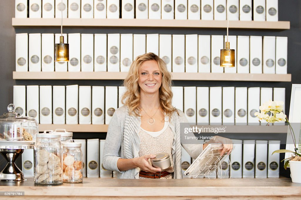 Portrait of female employee standing behind counter : Foto de stock