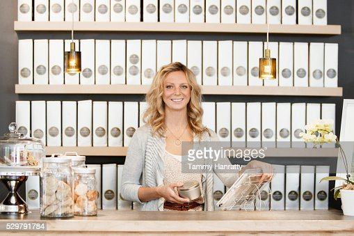 Portrait of female employee standing behind counter : Stock-Foto