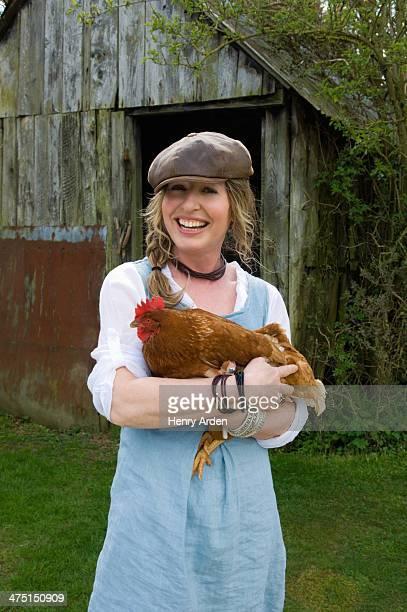 Portrait of female farmer holding hen