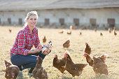 Portrait of female farmer with chicken