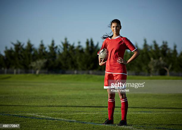 Portrait of female football player holding ball